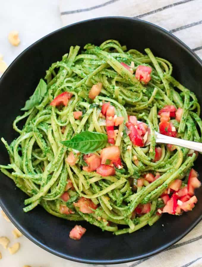 overhead photo of vegan pesto with chopped tomatoes and basil leaf