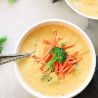 overhead shot of vegan broccoli and cheese soup in a white bowl with garnish of broccoli and shredded carrots