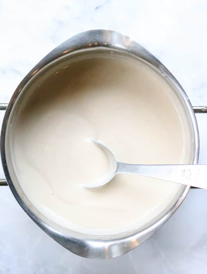 overhead shot of thickened cashew gravy in a silver pot