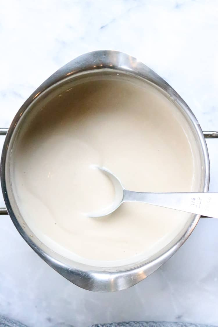 overhead shot of thickened vegan gravy in silver pot