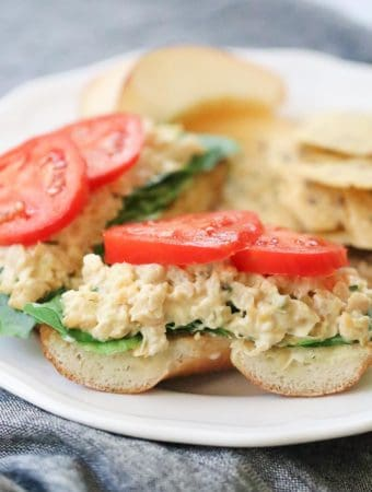 side closeup shot of vegan chickpea salad on half a bagel with lettuce and tomato