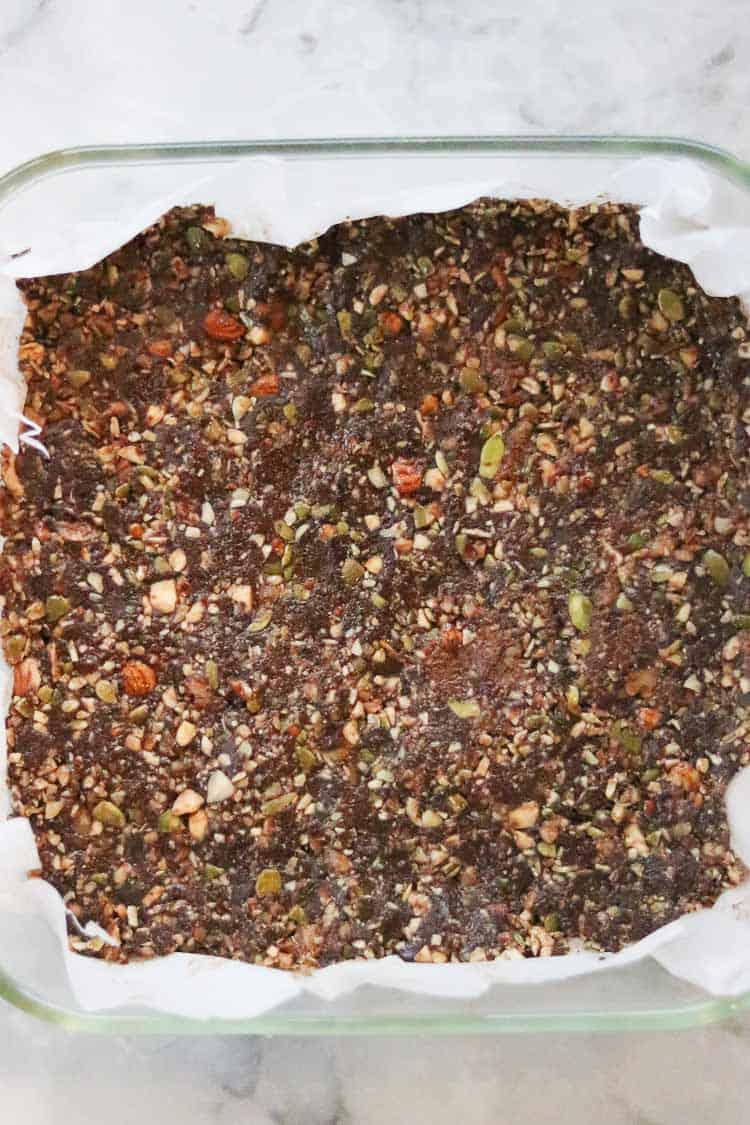 overhead view of gingersnap bar mixture pressed firmly into lined baking dish