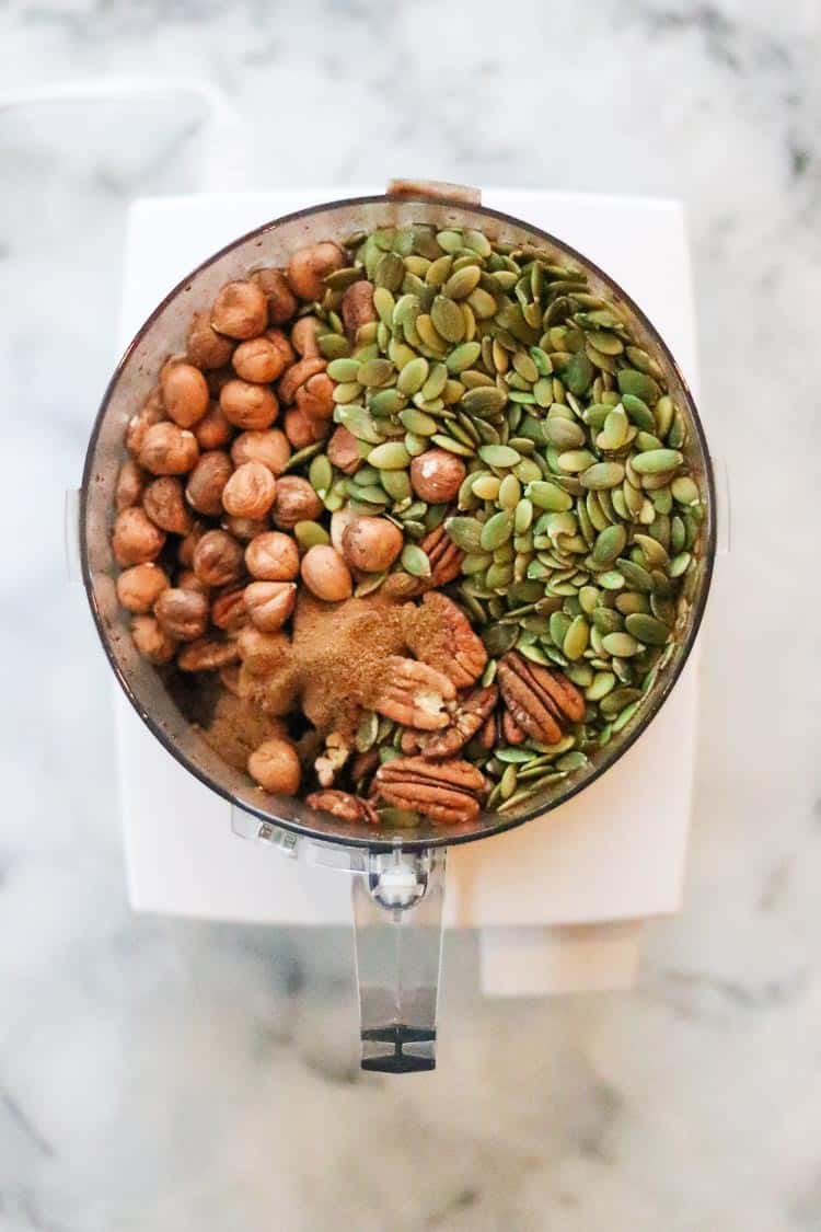 overhead view of nuts and seeds with spice mix in food processor bowl