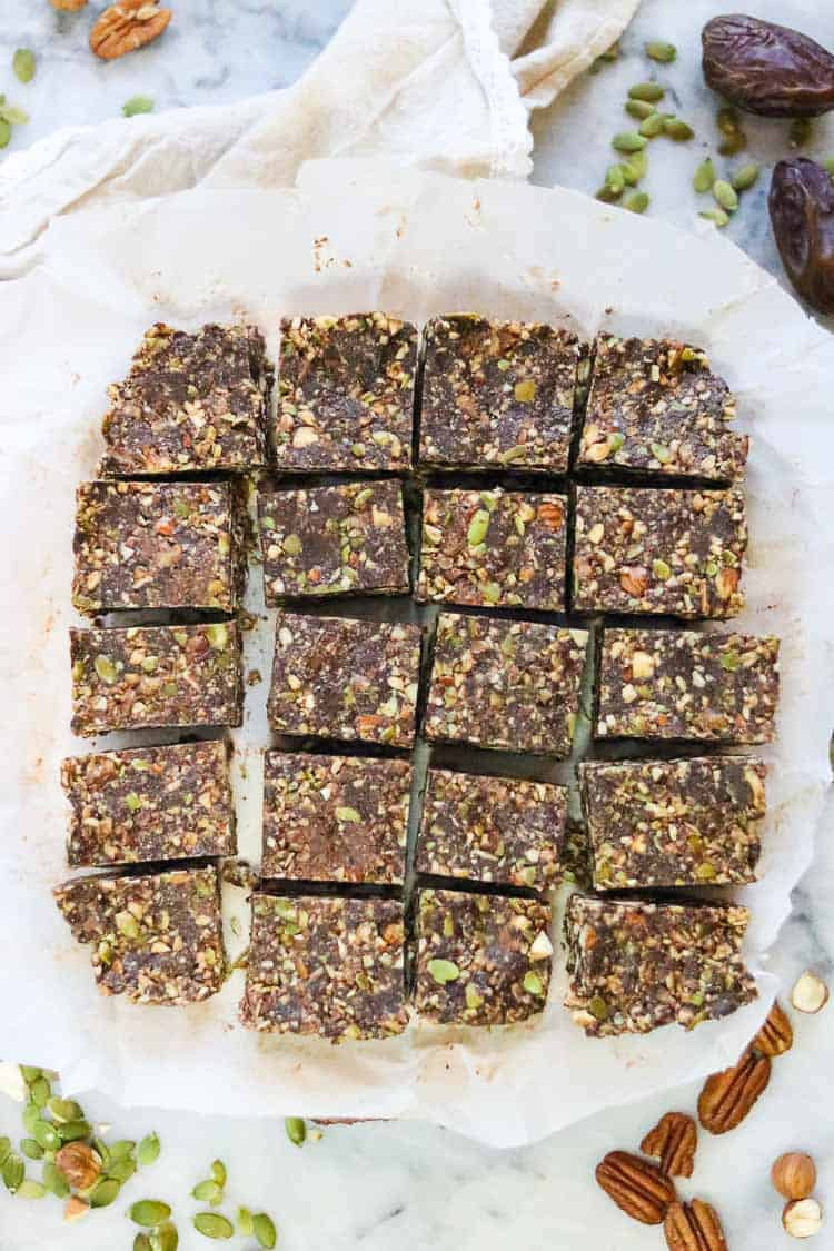 overhead shot of cut vegan chocolate gingersnap bars with nuts, dates, seeds, and napkin surrounding