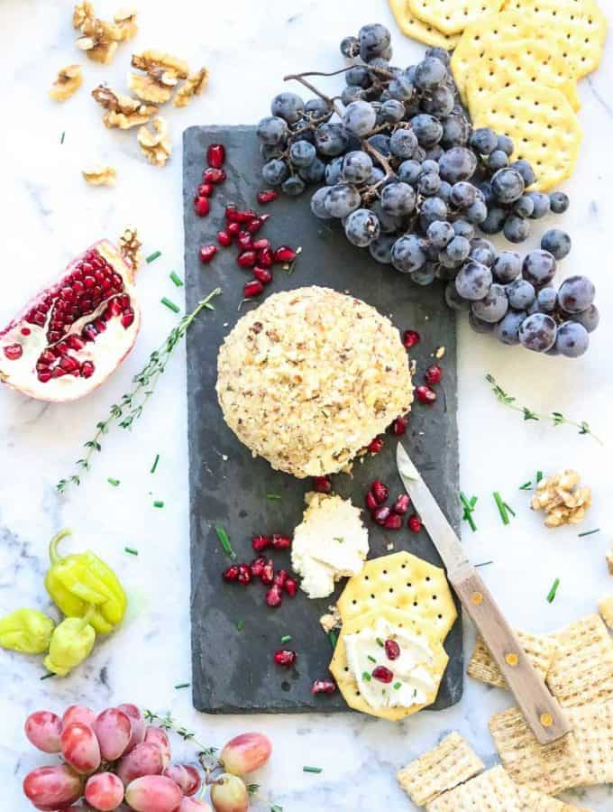 wide overhead shot of vegan cheese ball with crackers on black slate with pomegranates and grapes surrounding