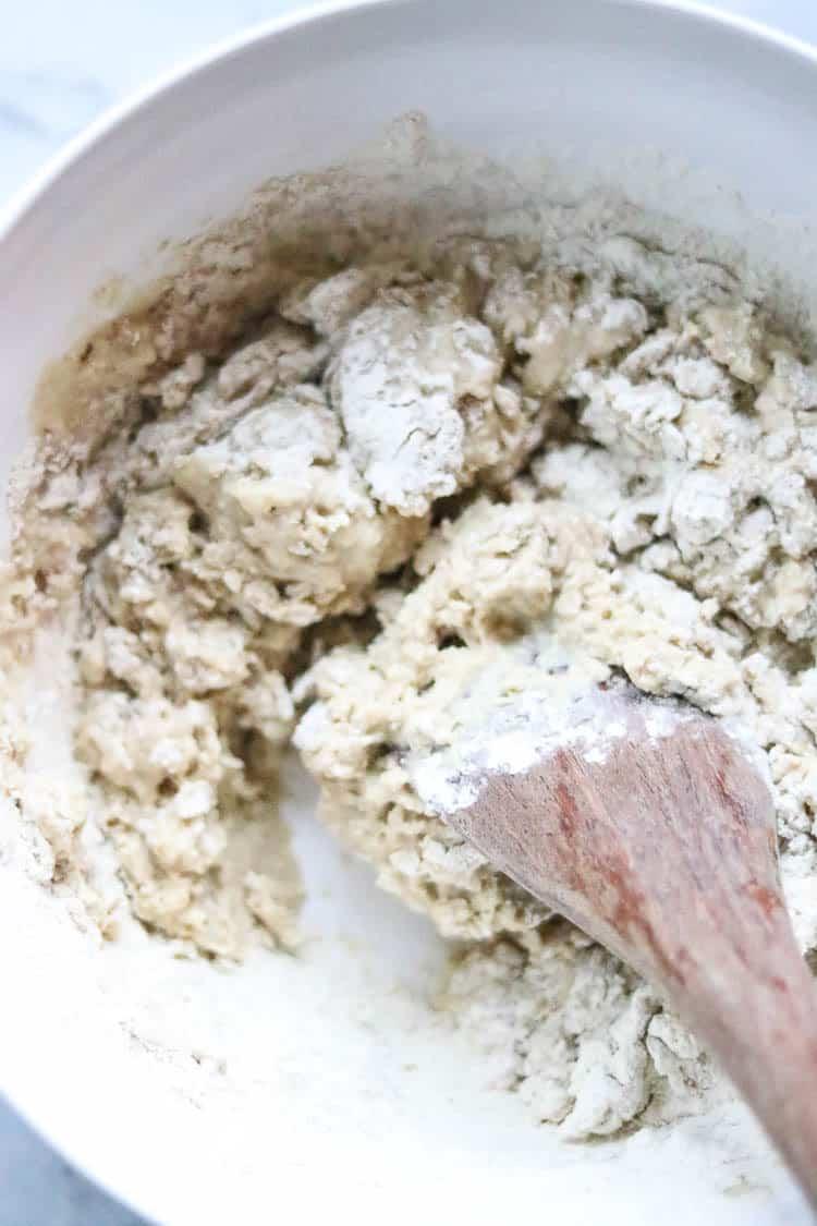 overhead shot of mixing gluten for vegan steaks with wooden spoon
