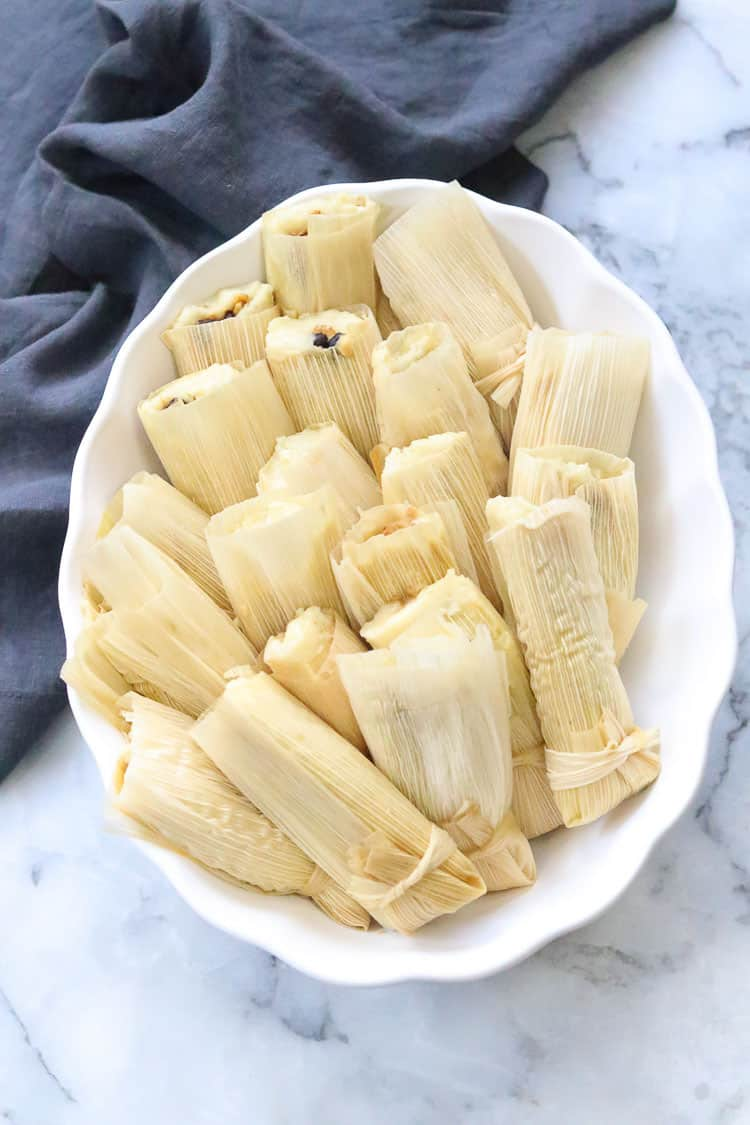 overhead shot of complete vegan tamales laying in fluted white serving dish with gray napkin behind