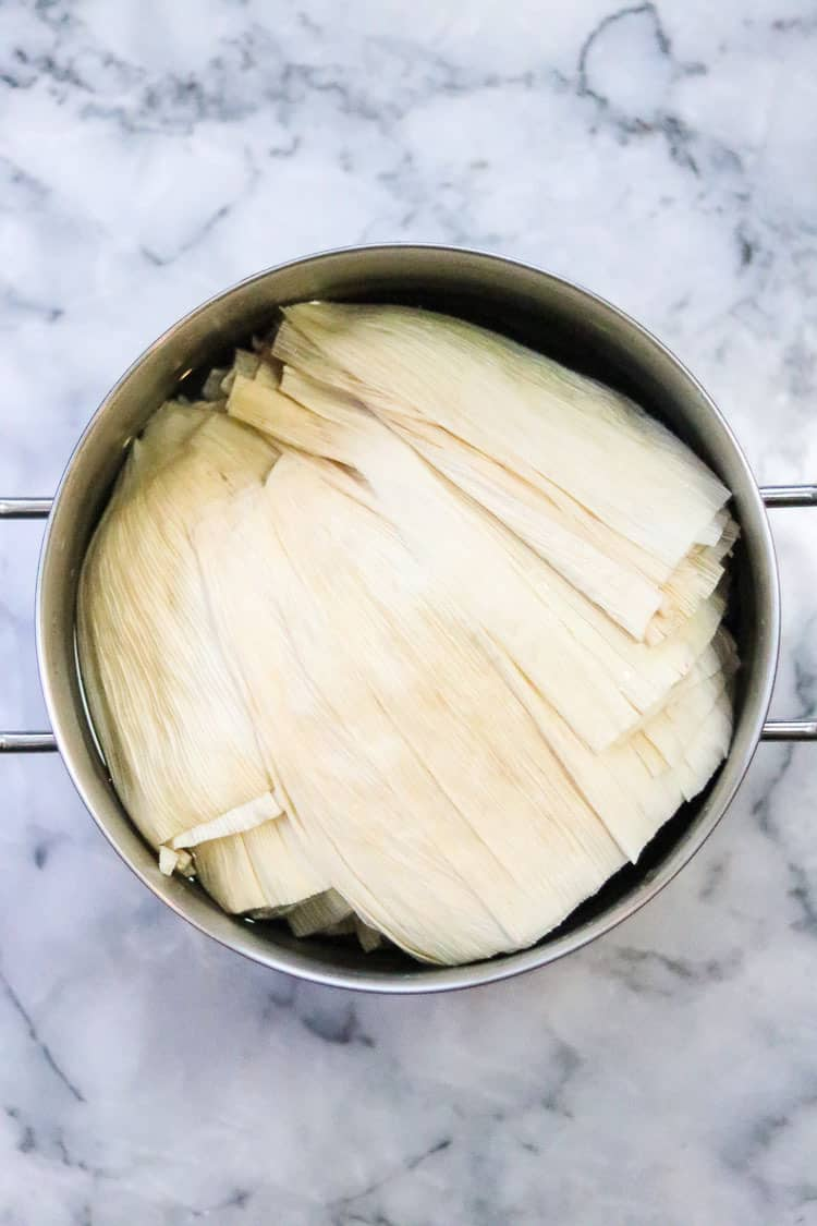 overhead shot of corn husks soaking in a large pot for vegan tamales