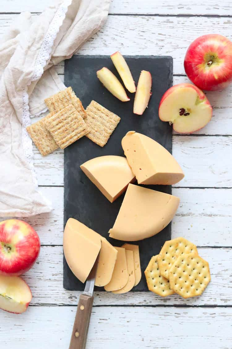 overhead shot of vegan cheddar cheese on a slate cheese board with apples and crackers surrounding