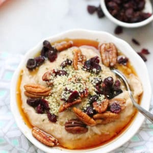 side overhead shot of bowl of buckwheat porridge garnished with cranberries, pecans, and hempseed on a diamond napkin