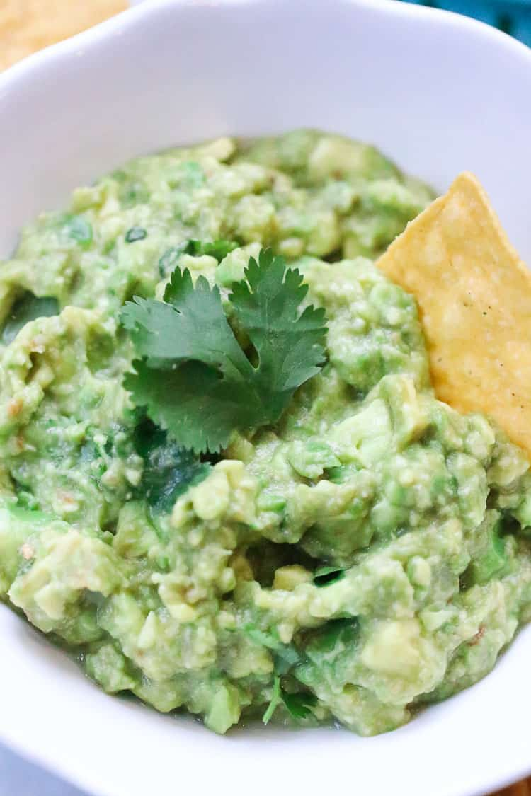overhead closeup shot of guacamole in a white bowl with a garnish of fresh cilantro