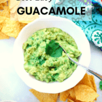 overhead shot of guacamole with chips, salsa, and festive napkin nearby image has text overlay for pinterest graphic