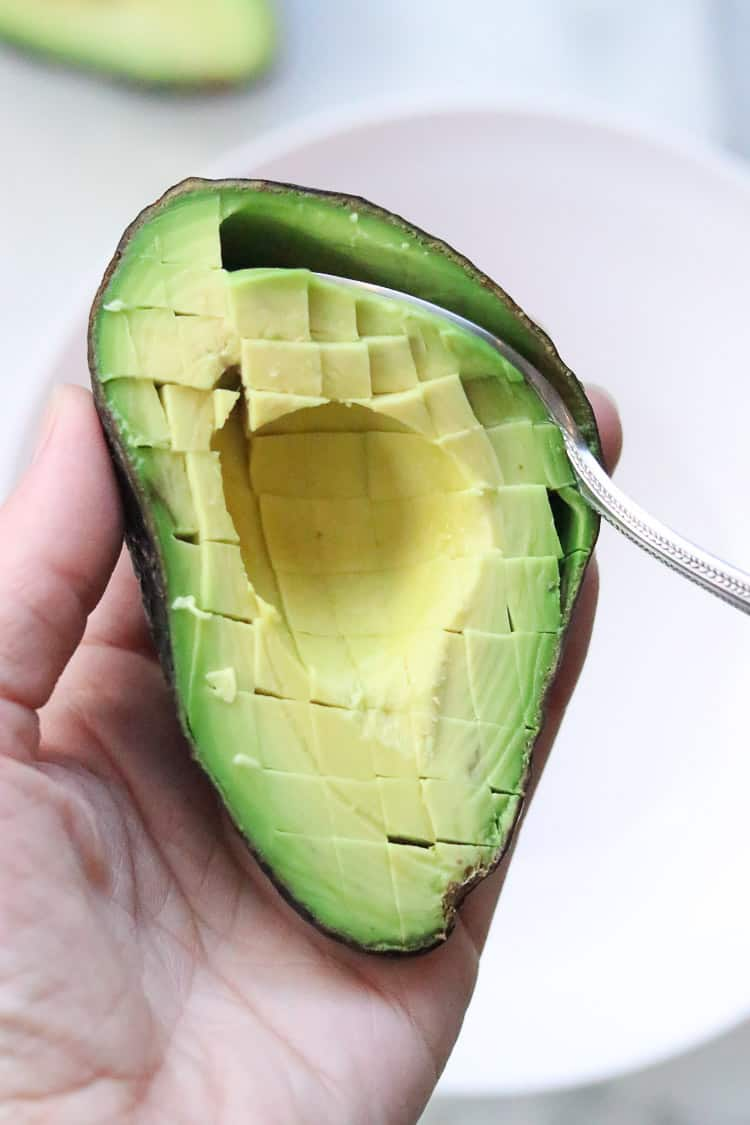 overhead shot of a hand holding half of an avocado with the pit removed and has been cut grid-style and a spoon is being used to removed avocado meat