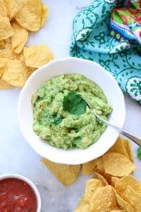 overhead shot of guacamole in a white dish with a garnish of cilantro and a silver spoon in it
