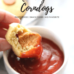 side overhead closeup shot of bitten corndog being dipped into ramekin of ketchup with text overlay