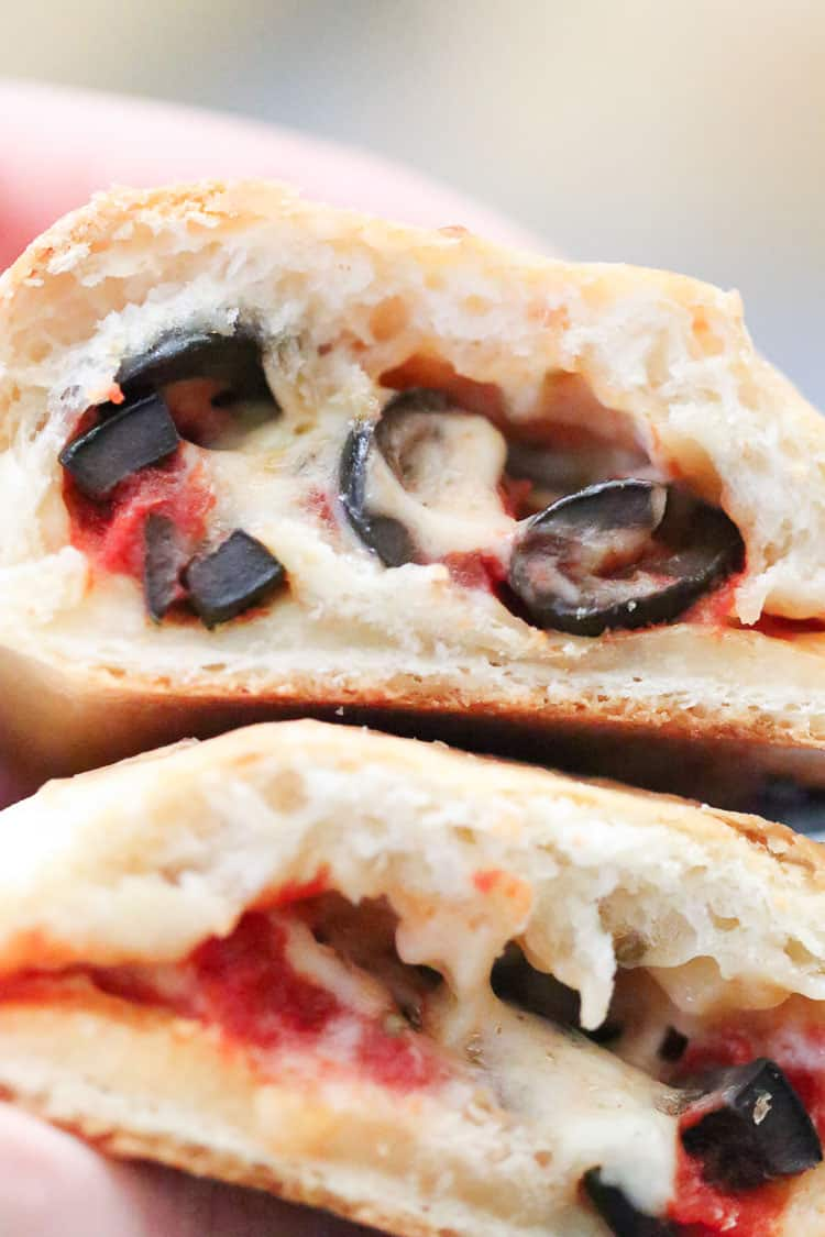 closeup overhead shot of halved vegan calzone showing melty cheese, sauce, and olives
