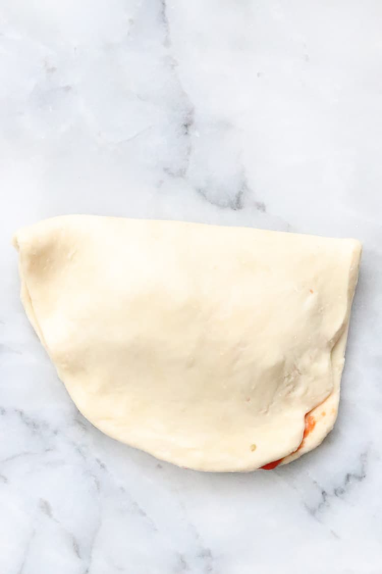 overhead shot of vegan calzone dough oval folded in half