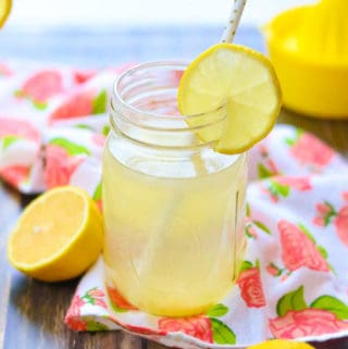 side shot of lemon water in a jar with cut lemon on jar rim and white straw in it