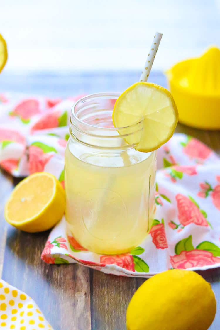 side overhead shot of mason jar glass of lemon water with halved lemon beside on wooden surface with lemon squeezer in background