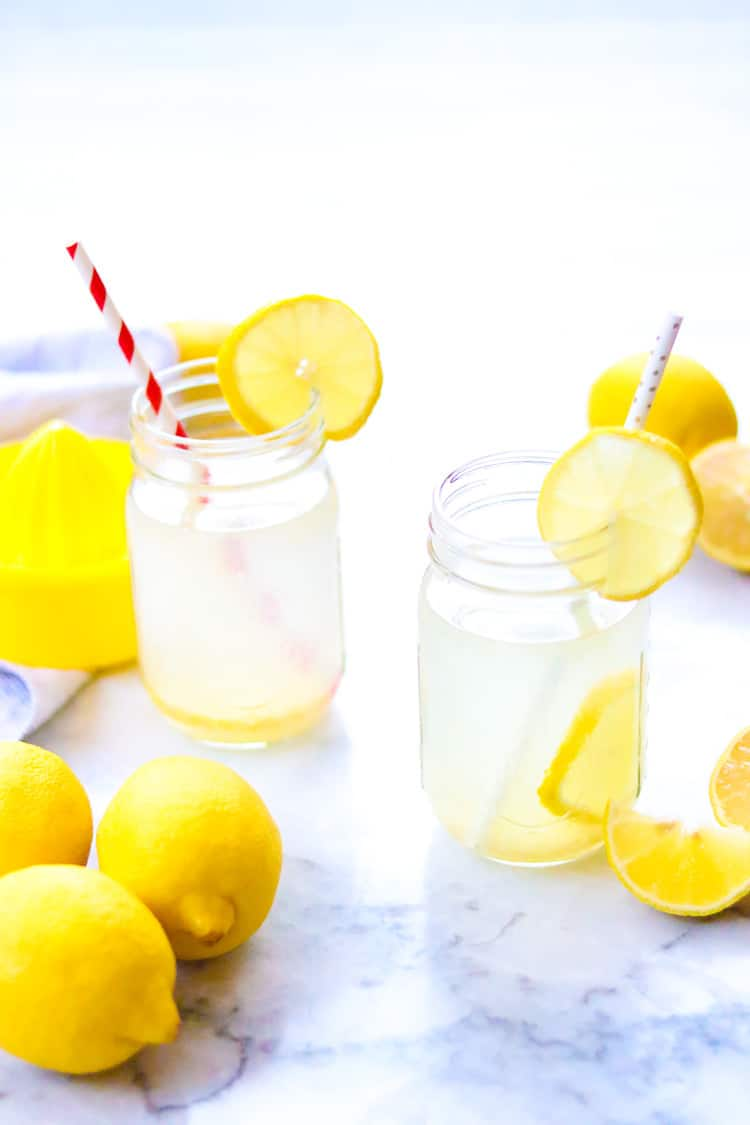 side overhead shot of two mason jars filled with lemon water, lemon slices on edge of jars, and straws in them
