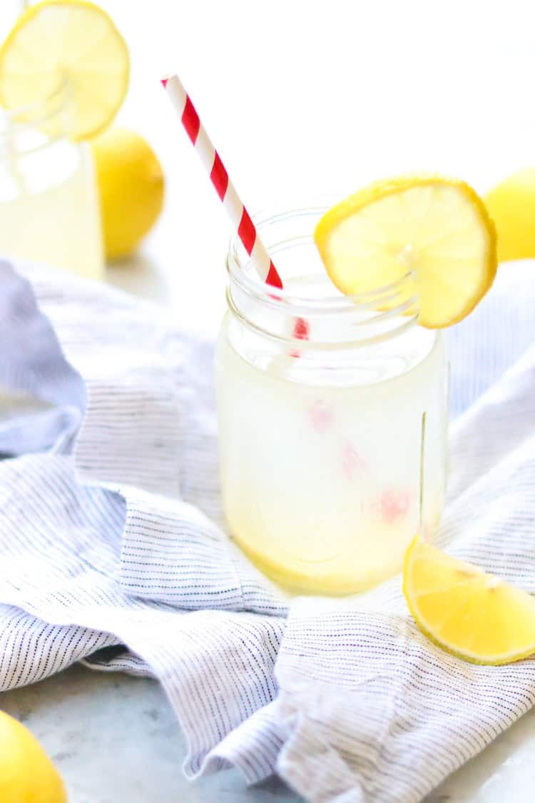 side overhead shot of single glass of lemon water with lemon wedge beside on blue striped napkin and second glass in background