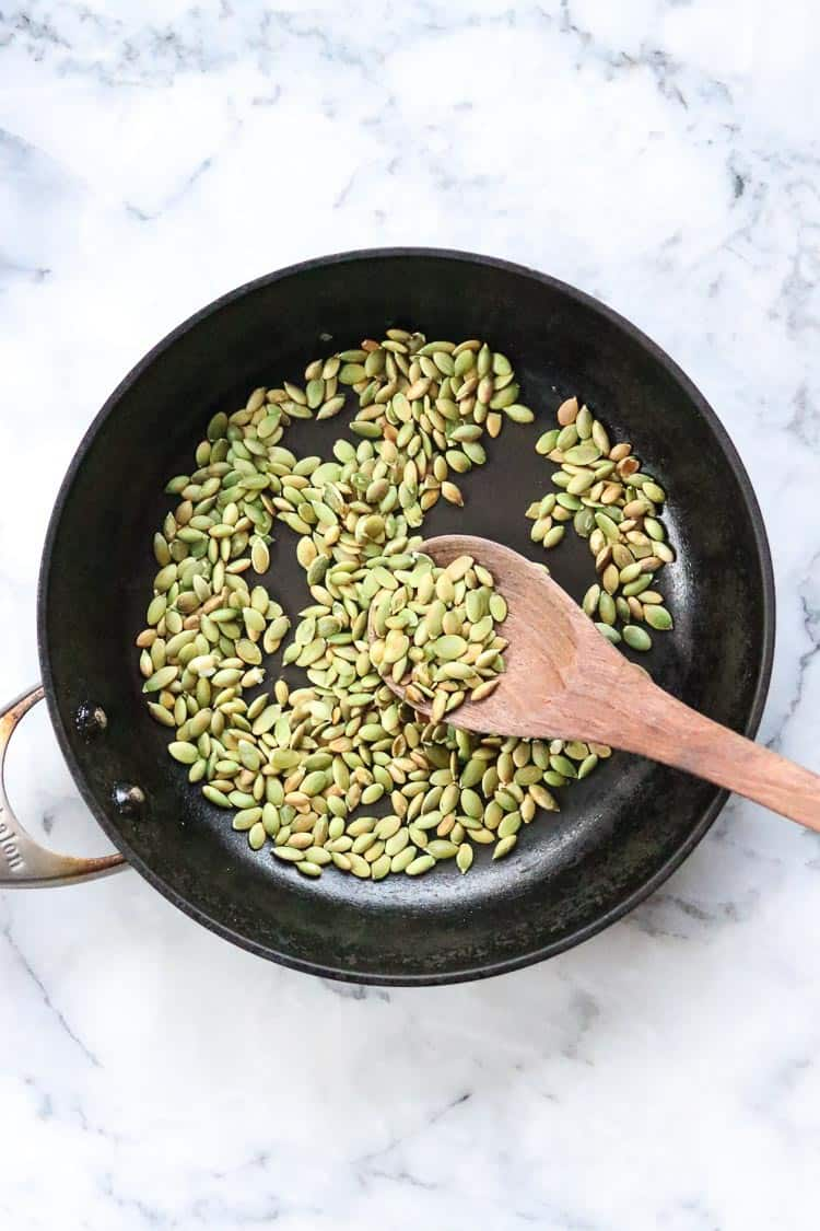 overhead shot of pumpkin seeds in frying pan for toasting with wooden spoon