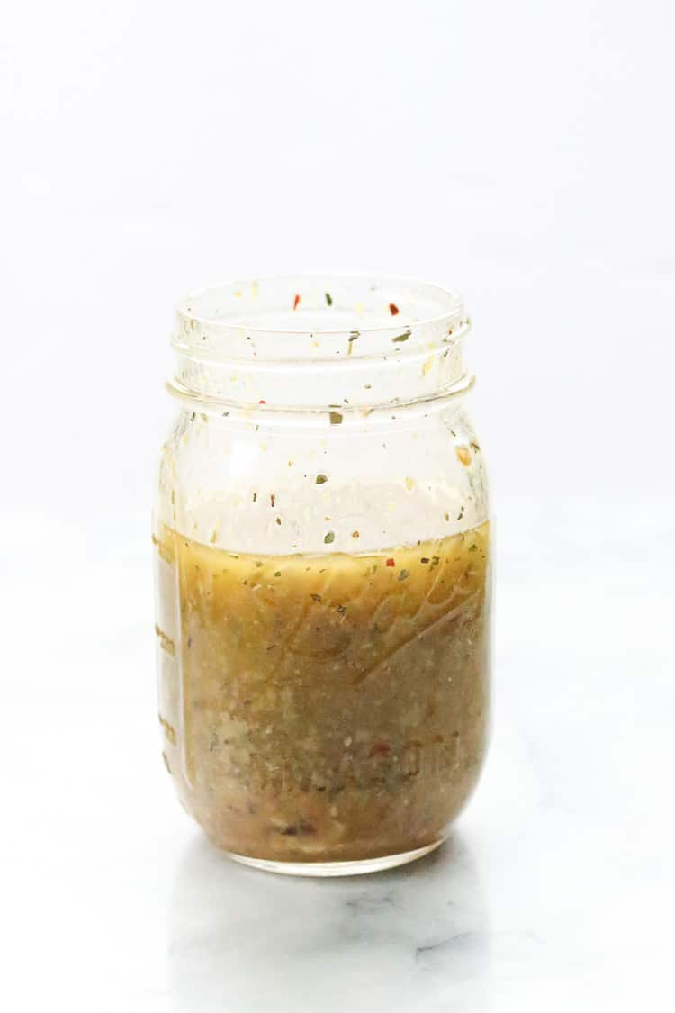 side shot of homemade Italian dressing ingredients mixed in a pint sized mason jar