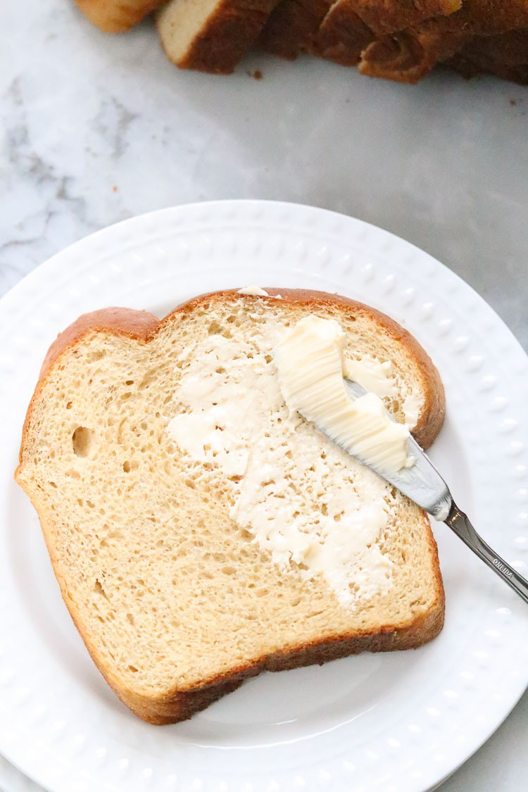 overhead shot of a slice of whole wheat bread on a white plate being spread with margarine