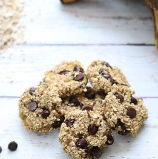 overhead shot of banana oat cookies in a pile with bananas oats and chocolate chips nearby