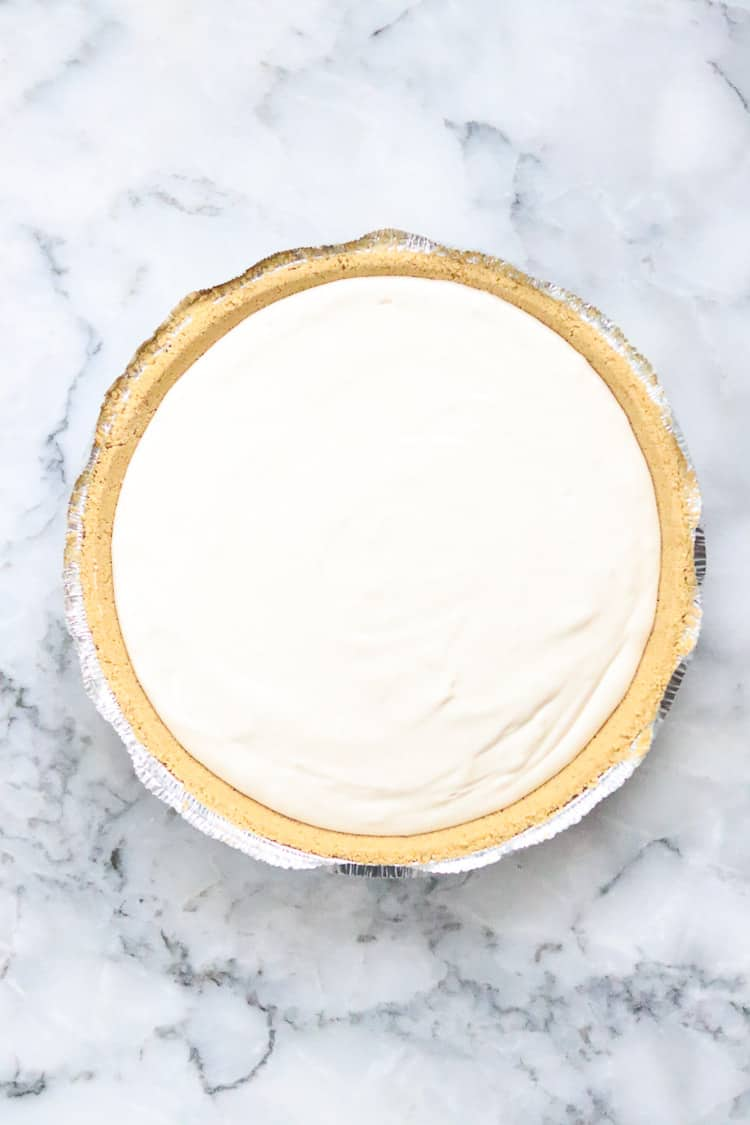 overhead shot of unbaked vegan cheesecake in a graham cracker pie crust