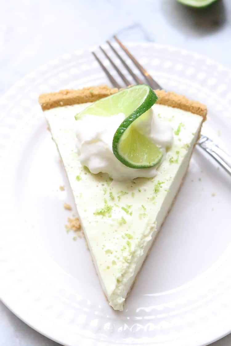 overhead closeup shot of one slice of vegan key lime pie on white plate with a fork