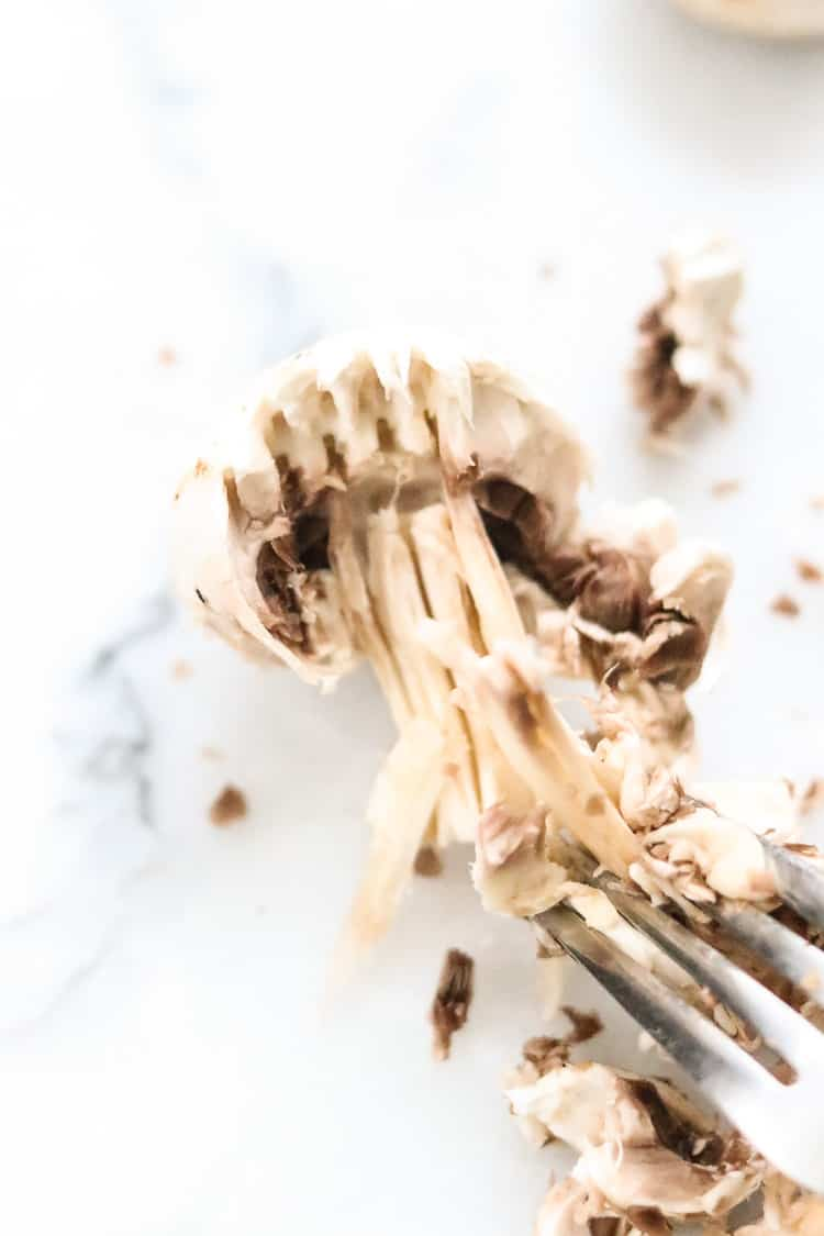 overhead closeup shot of button mushroom being shredded with a fork for mushroom sandwich