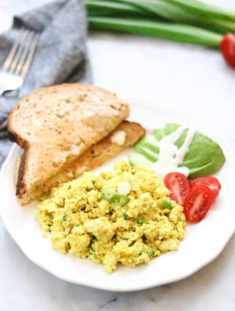 side overhead shot of tofu scramble on a white plate with toast, avocado and sliced tomatoes