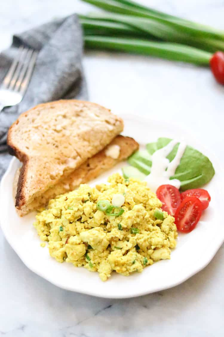 side overhead shot of tofu scramble on a white plate with sliced avocado and toast with napkin beside