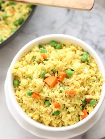overhead closeup shot of vegan fried rice in white double bowl with skillet in background and wooden spoon