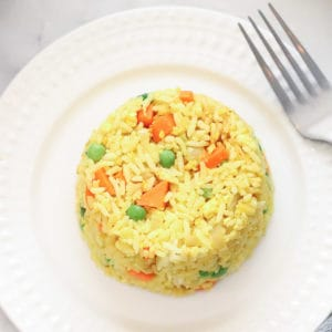 overhead shot of vegan fried rice in a round shape on a white plate with carrots and peas