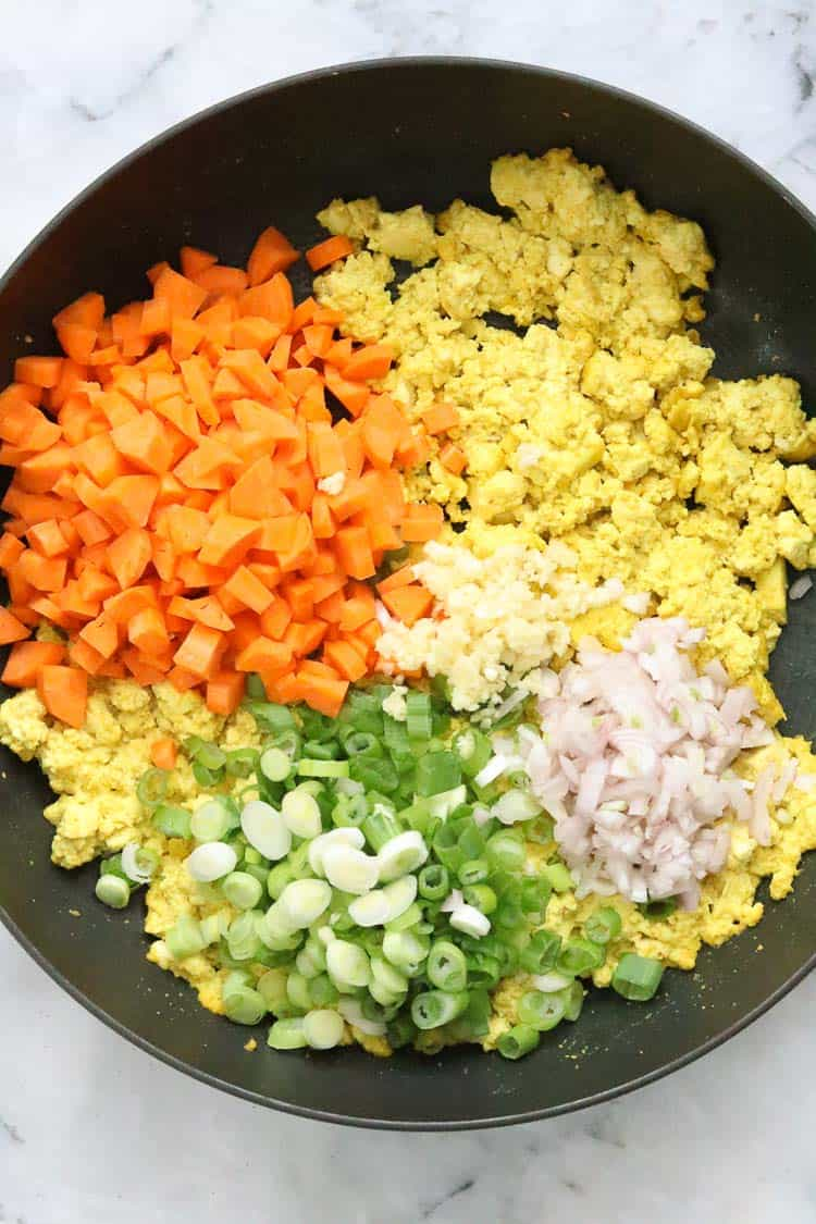 overhead shot of diced carrots, green onions, garlic and shallot being added to tofu for vegan fried rice