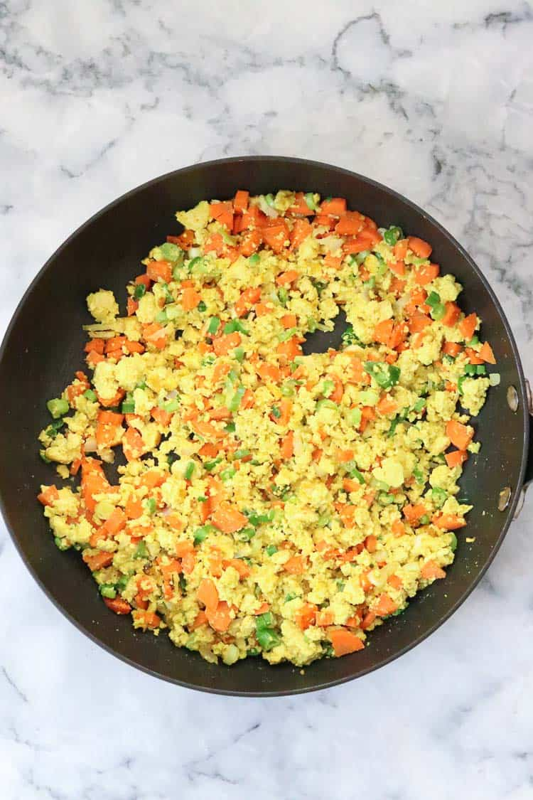 overhead shot of tofu and veggies all mixed in black skillet to season vegan fried rice