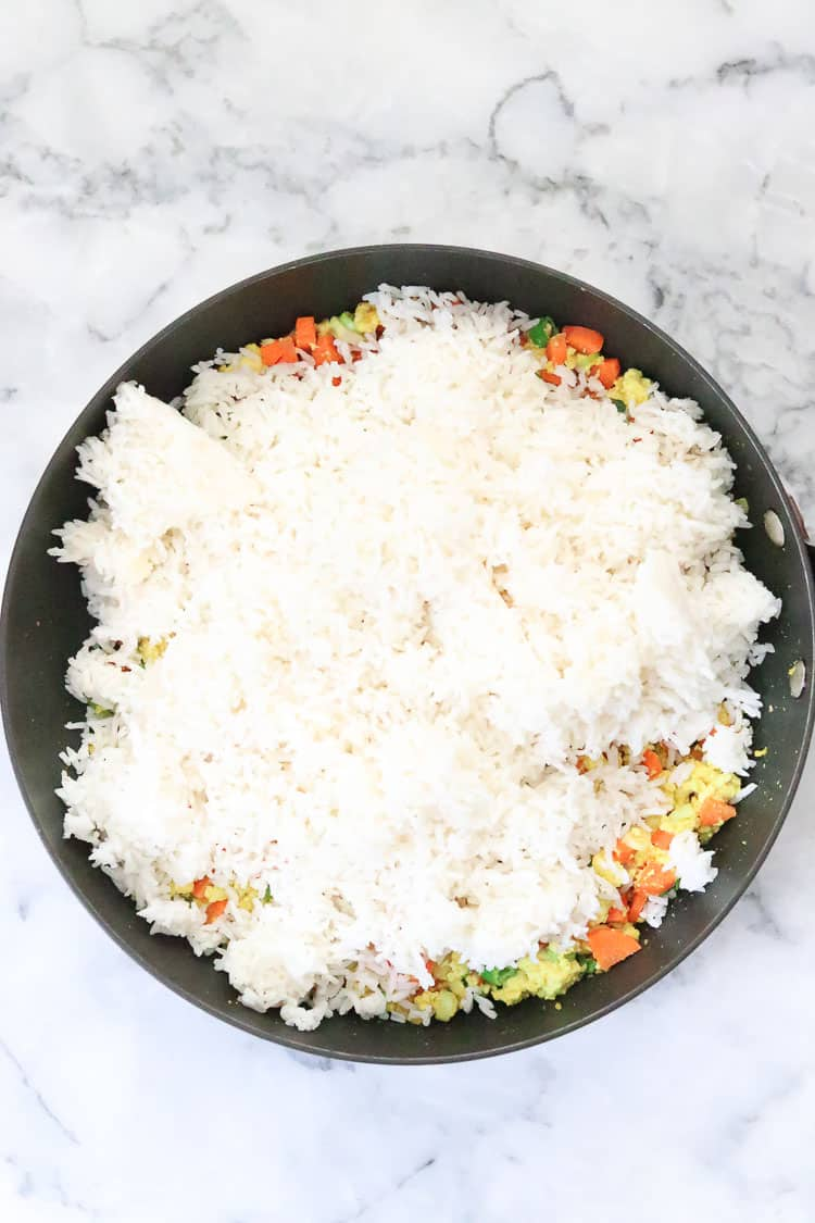 over head process shot of white jasmine rice added to veggies and tofu