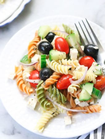 overhead closeup shot of vegan pasta salad on a white plate with a fork