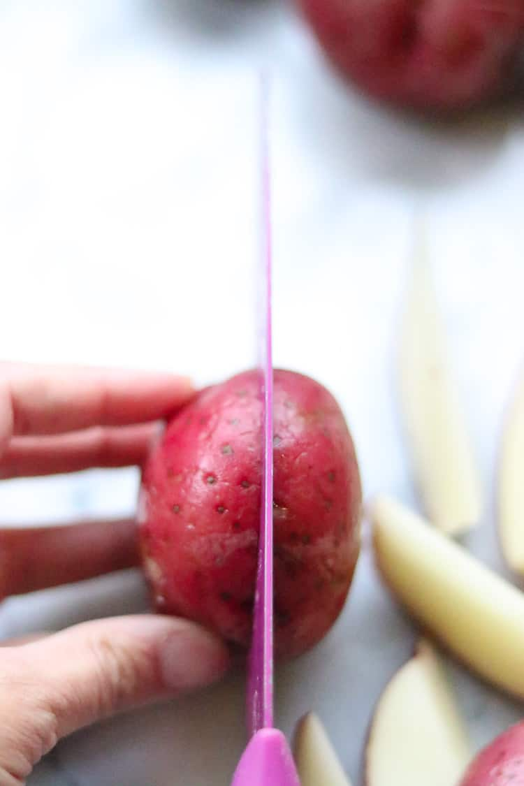 overhead shot of potato being cut with wedges at the side