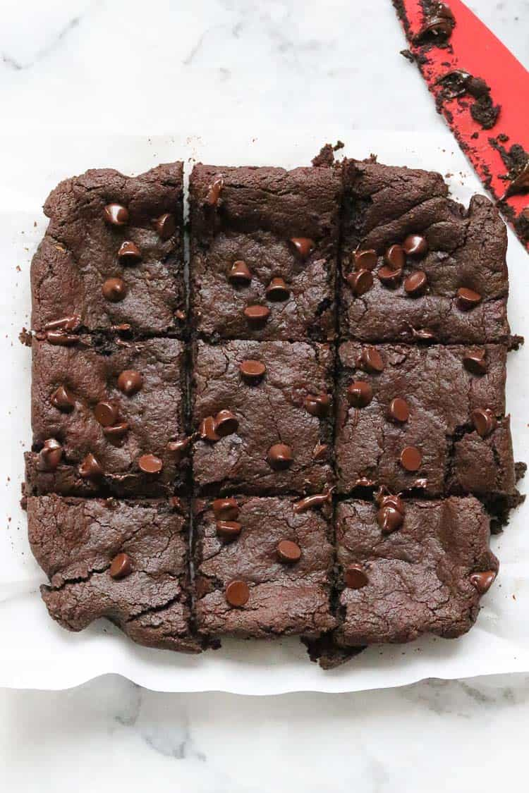 overhead photo of vegan avocado brownies on white parchment paper sliced with a red knife