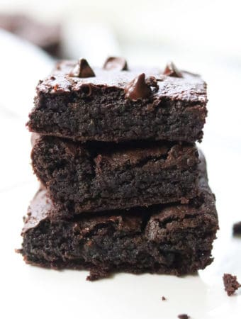 side shot of vegan avocado brownies stacked three high with text overlay for pinterest
