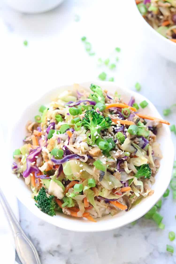 side overhead shot of one bowl of vegan egg roll insides on top of white rice garnished with chopped green onion