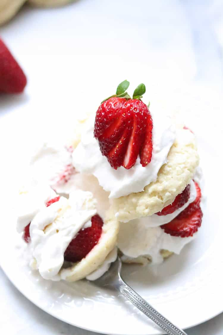 vegan strawberry shortcake on a white plate with sliced strawberry on top and fork full beside
