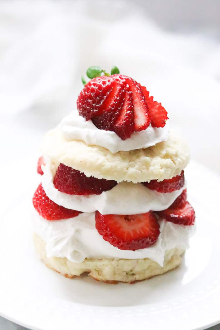 side overhead shot of vegan shortcake stacked high with coconut whip cream and strawberries
