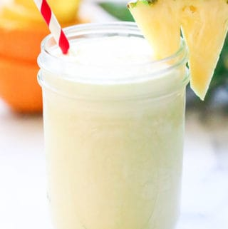 side shot of virgin pina colada with coconut milk in a mason jar with striped straw and pineapple slice