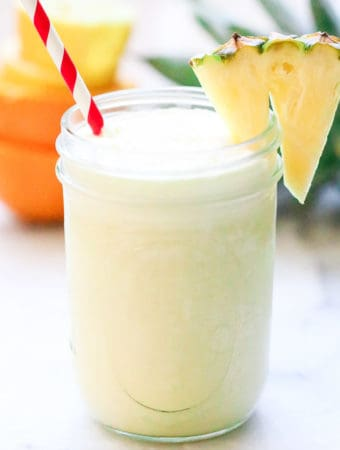 side shot of virgin pina colada in a mason jar with striped straw and pineapple slice