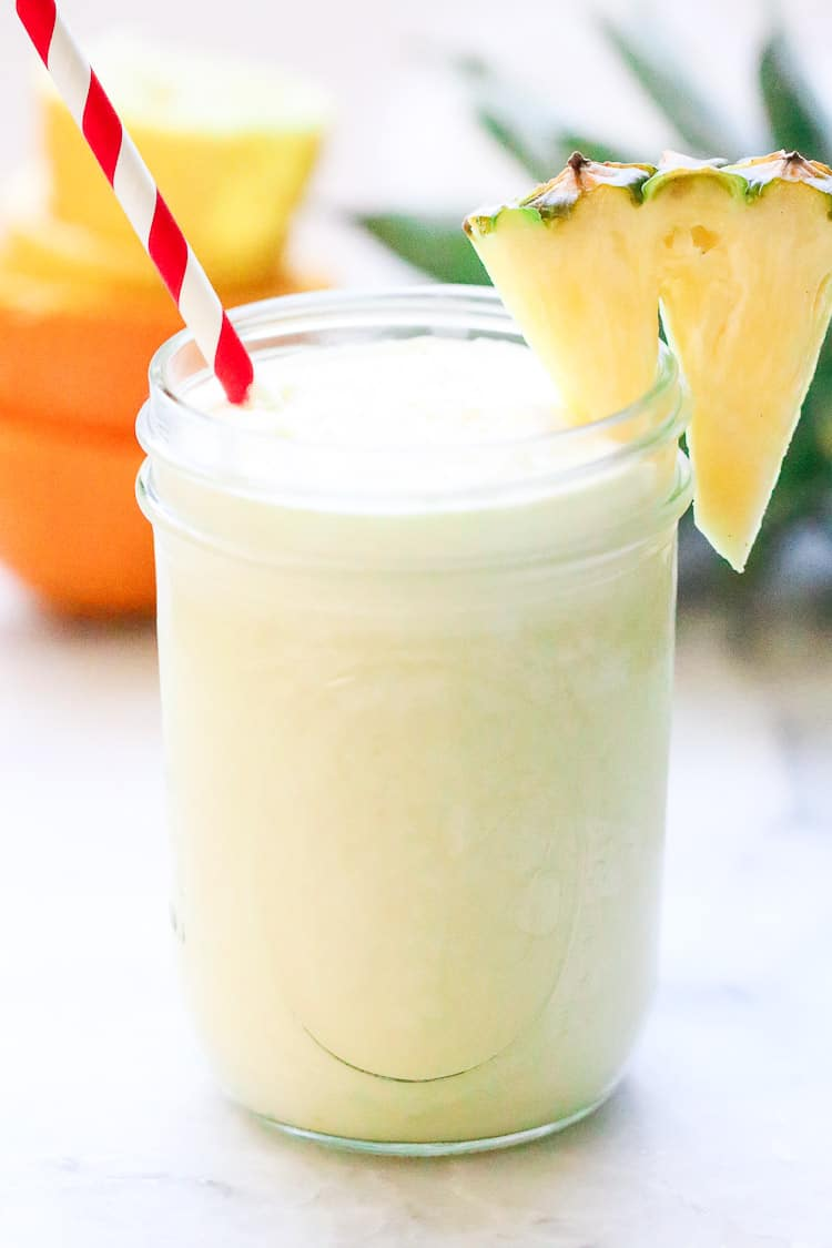 side shot of virgin pina colada smoothie in a pint jar with striped straw and pineapple slice on the side
