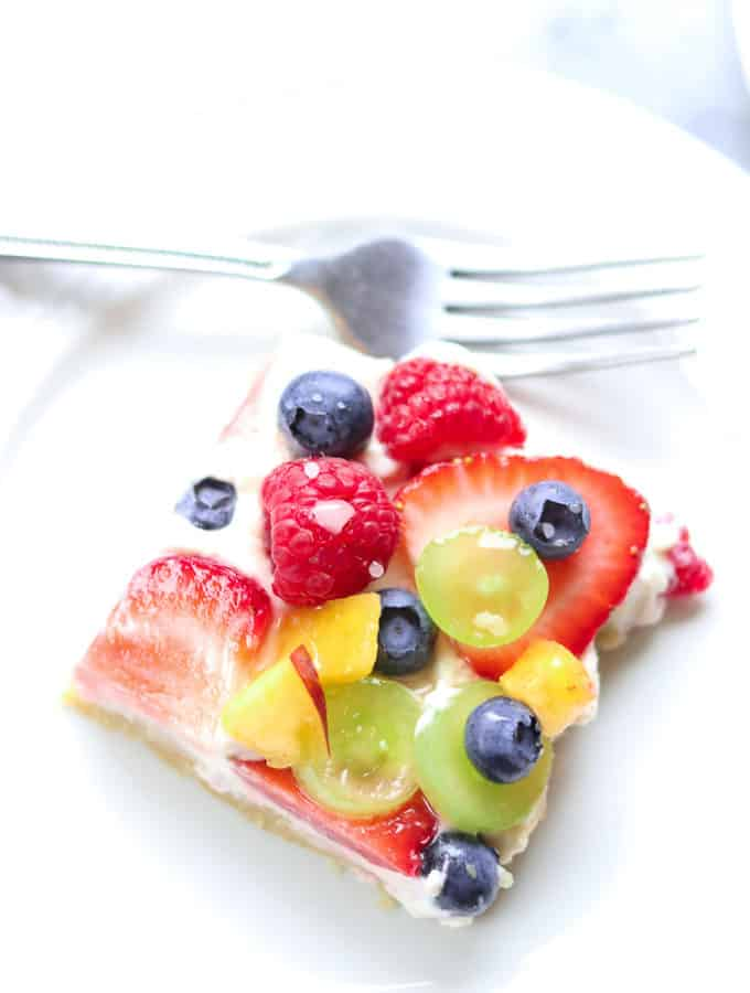 overhead closeup shot of a slice of vegan fruit pizza with raspberries, strawberries, blueberries, and grapes